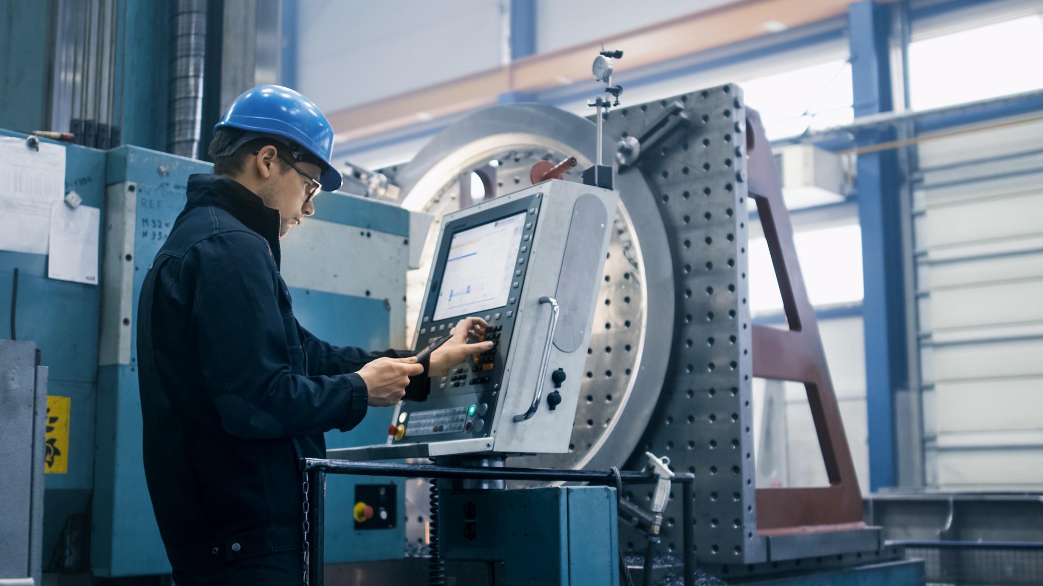 Industri 4.0, Ein Arbeiter in einer Fabrik nutzt ein Tablet