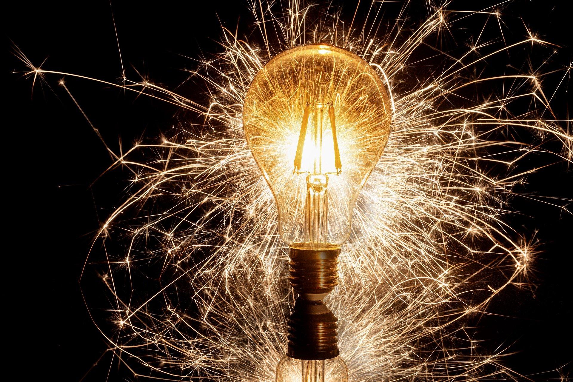 Symbolbild Innovation und Ideen: Funken sprühen aus eine Glühlampe.
