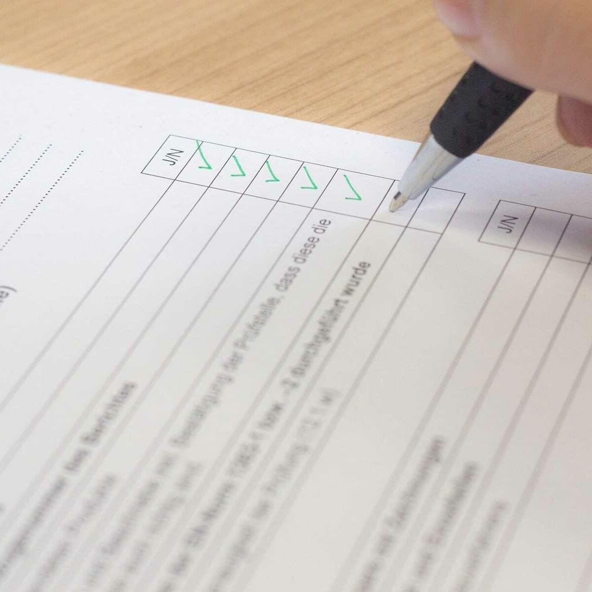 Bild einer Papier-Checkliste, die gerade ausgefüllt wird. Einige Punkte sind bereits abgehakt.