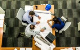 Drei Personen sitzen am Tisch für ein Meeting zusammen