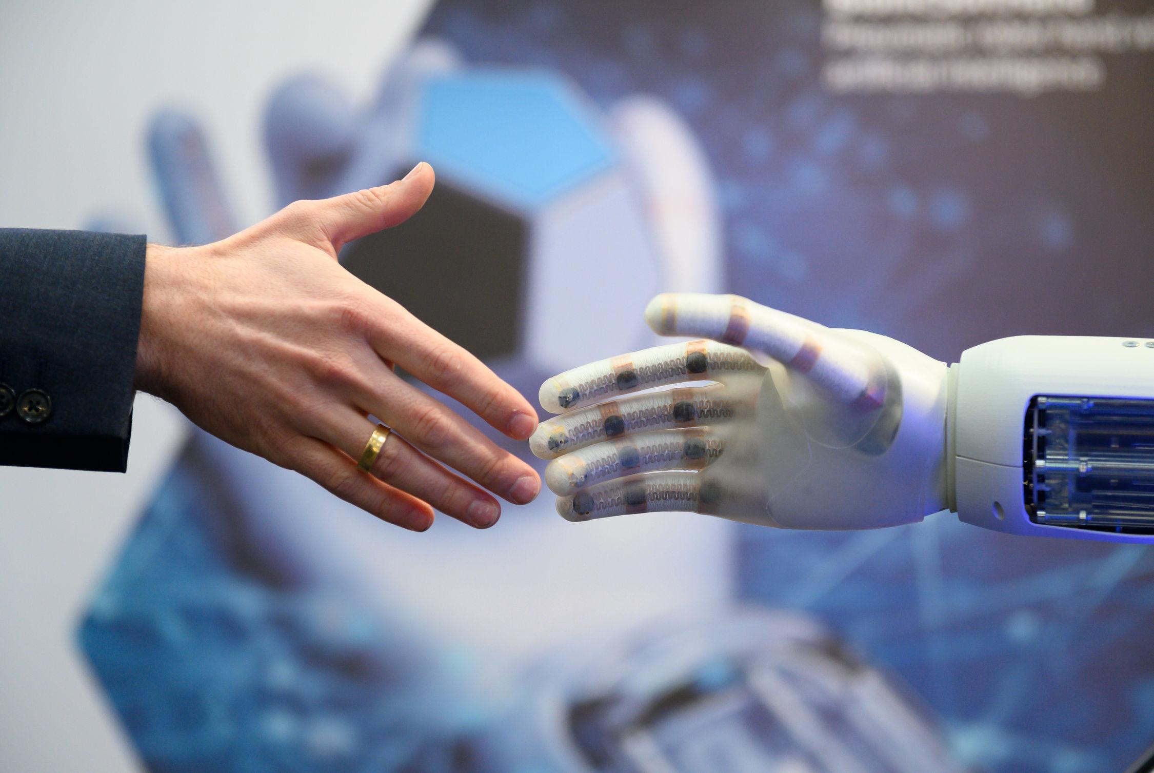 Eine menschliche und eine Roboterhand begegnen sich bei der Hannover Messe