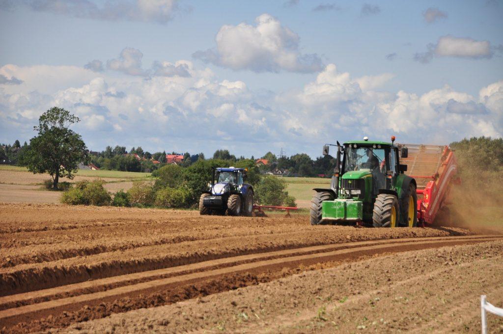 Zwei Traktoren bei der Ernte auf dem Acker.