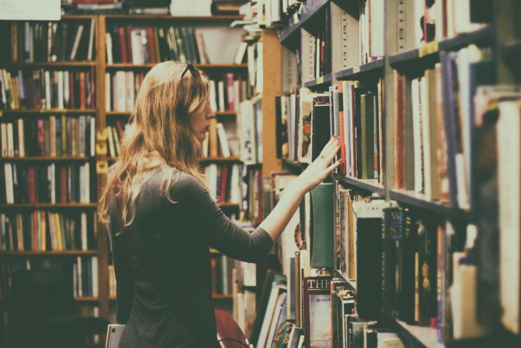 Eine Frau steht an einem Bücherregal in einer Buchhandlung.