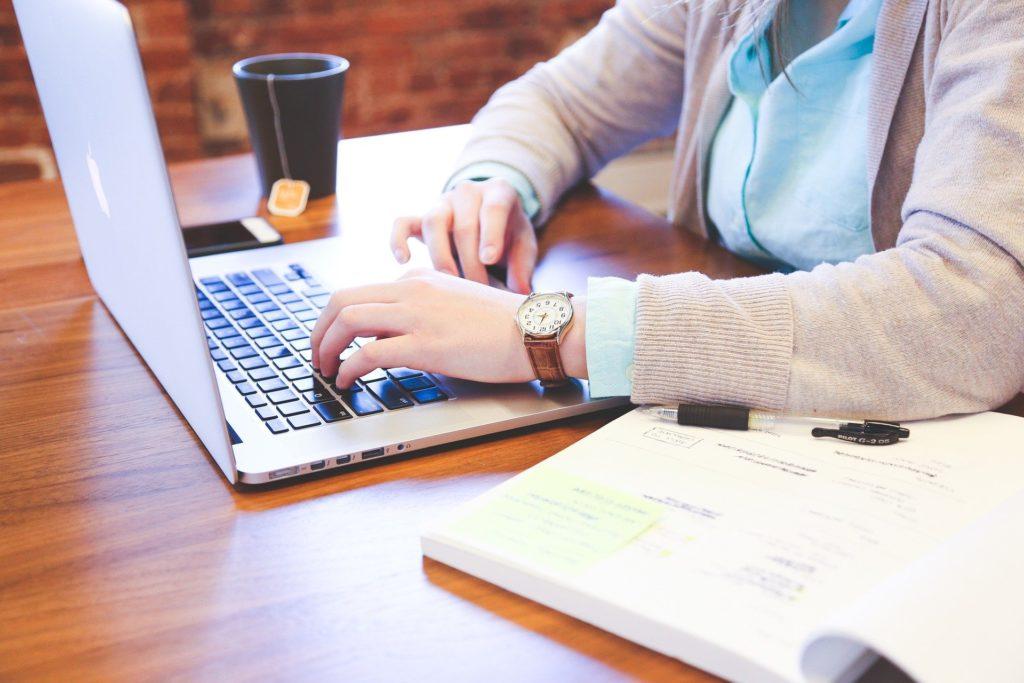Eine Person sitzt am Schreibtisch und arbeitet am Laptop.