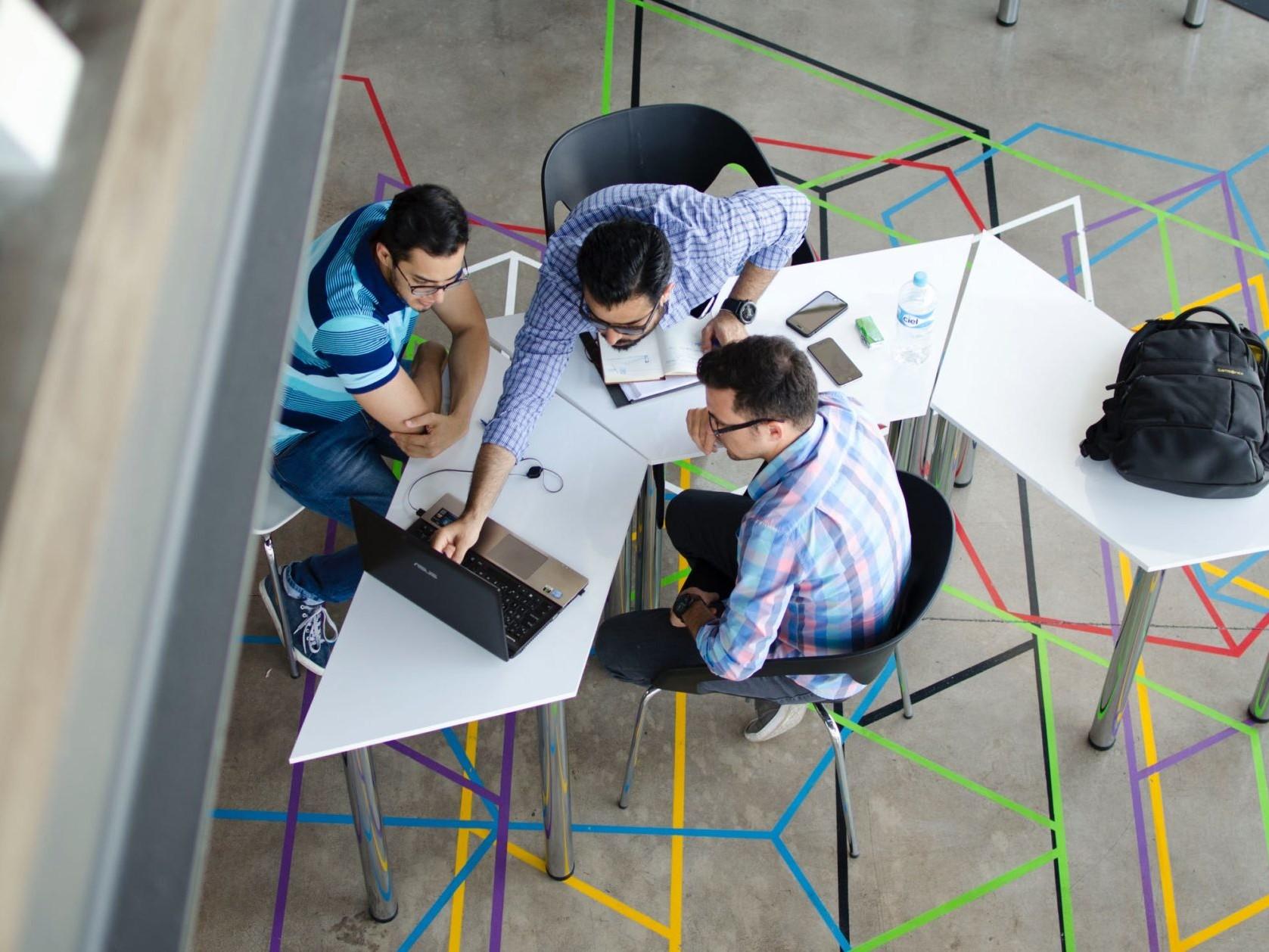 Eine Gruppe junger Männer sitzt am Tisch und berät am Laptop.