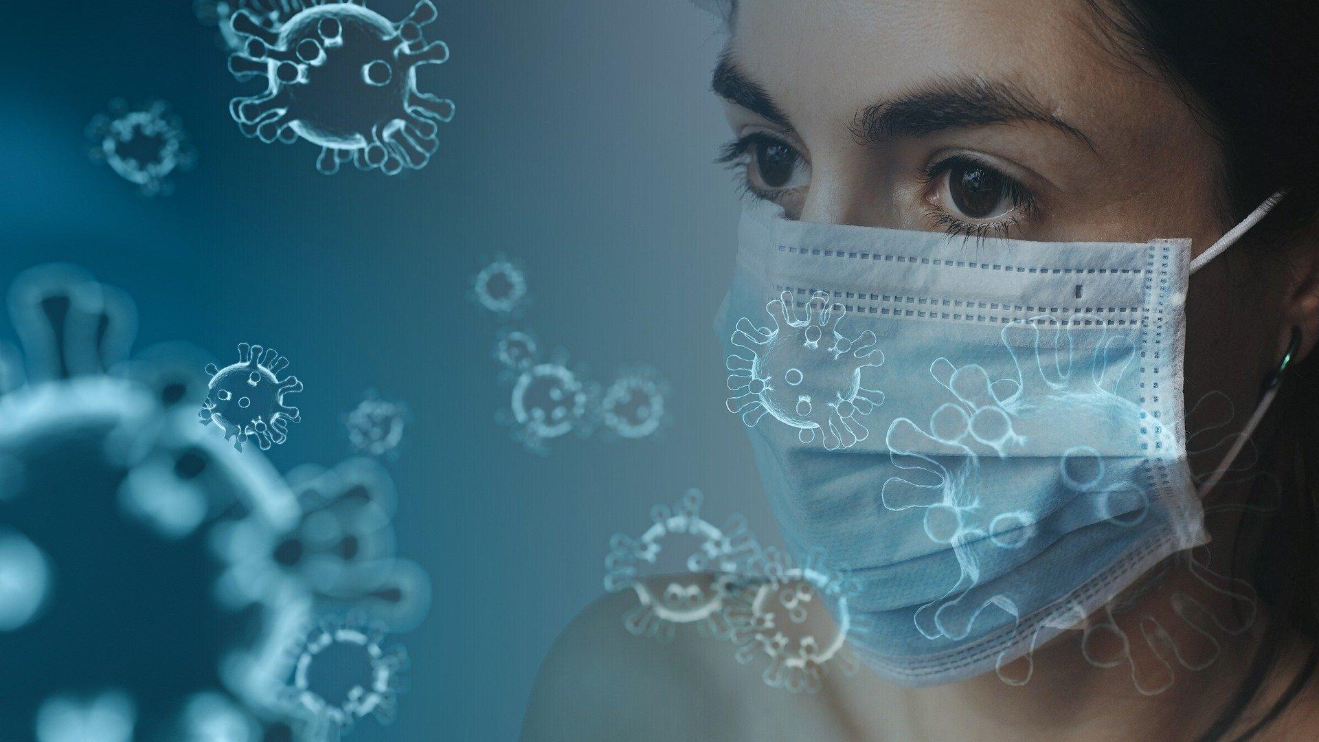 Symbolfoto Coronavirus: Viren fliegen um eine Frau mit Schutzmaske