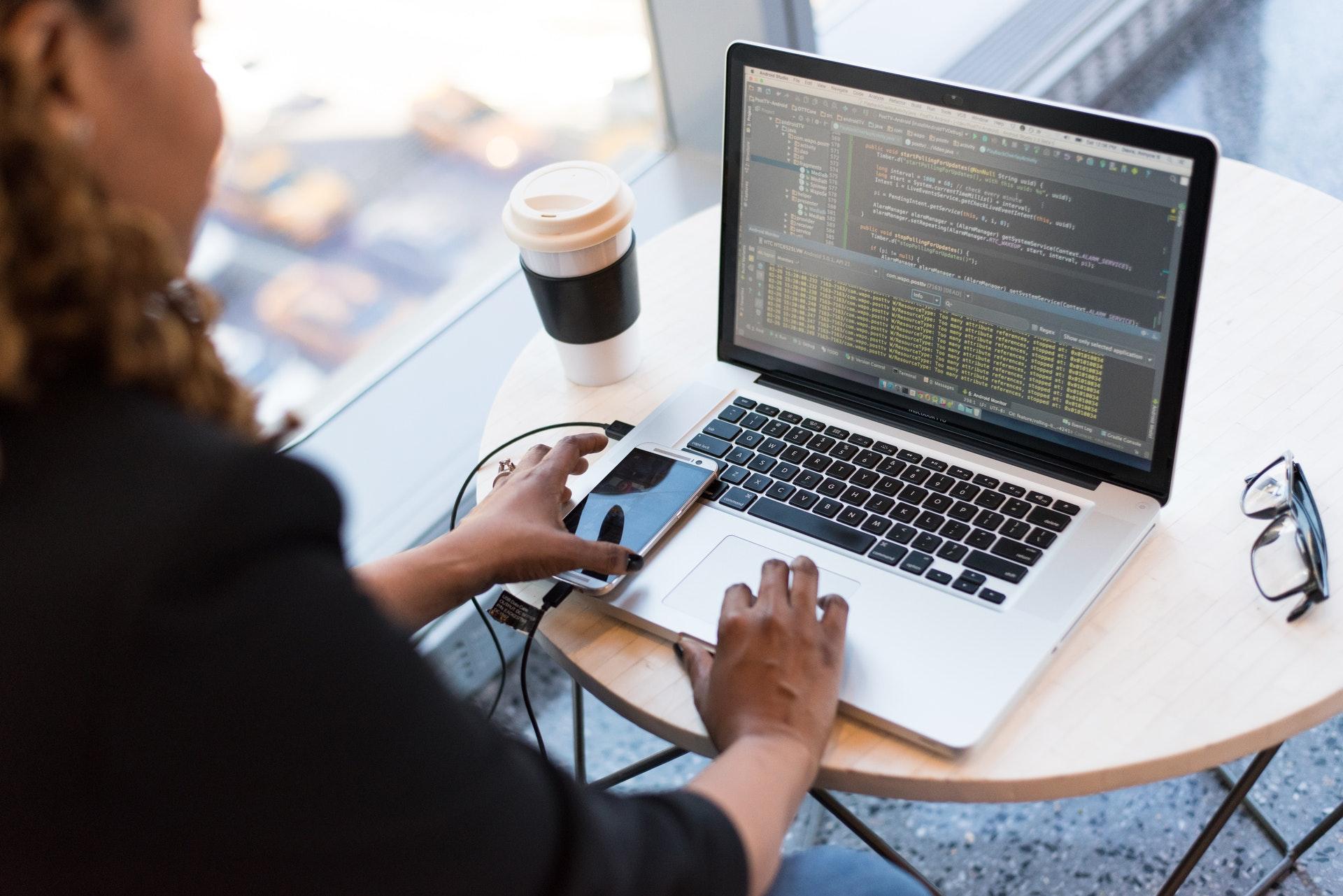 Frau sitzt mit Handy und Kaffee vorm Laptop.