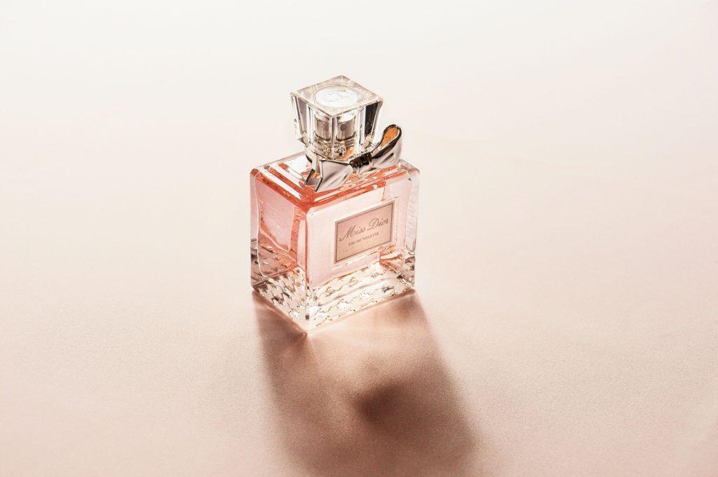 Rosa Parfumflasche auf rosa Untergrund.