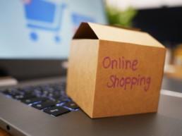 Kleines Paket mit der Aufschrift Online Shopping auf einer Laptoptastatur.