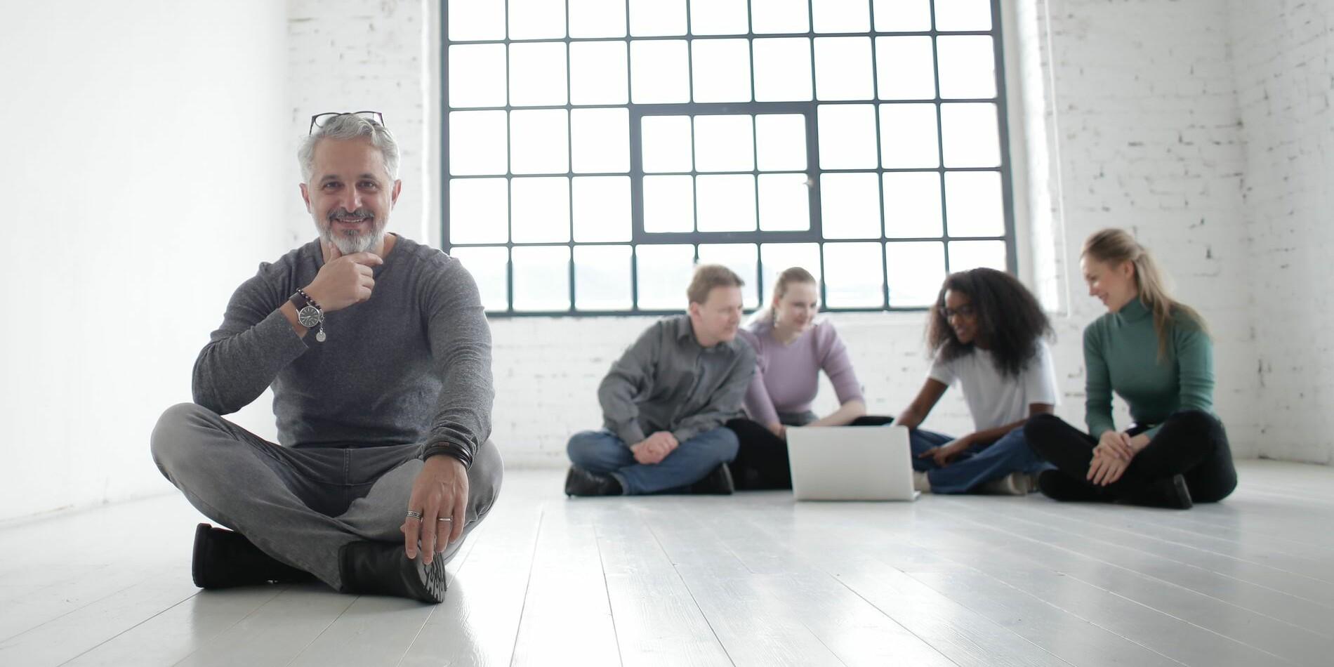 Fünf Leute sitzen auf dem Boden um einen Laptop herum.