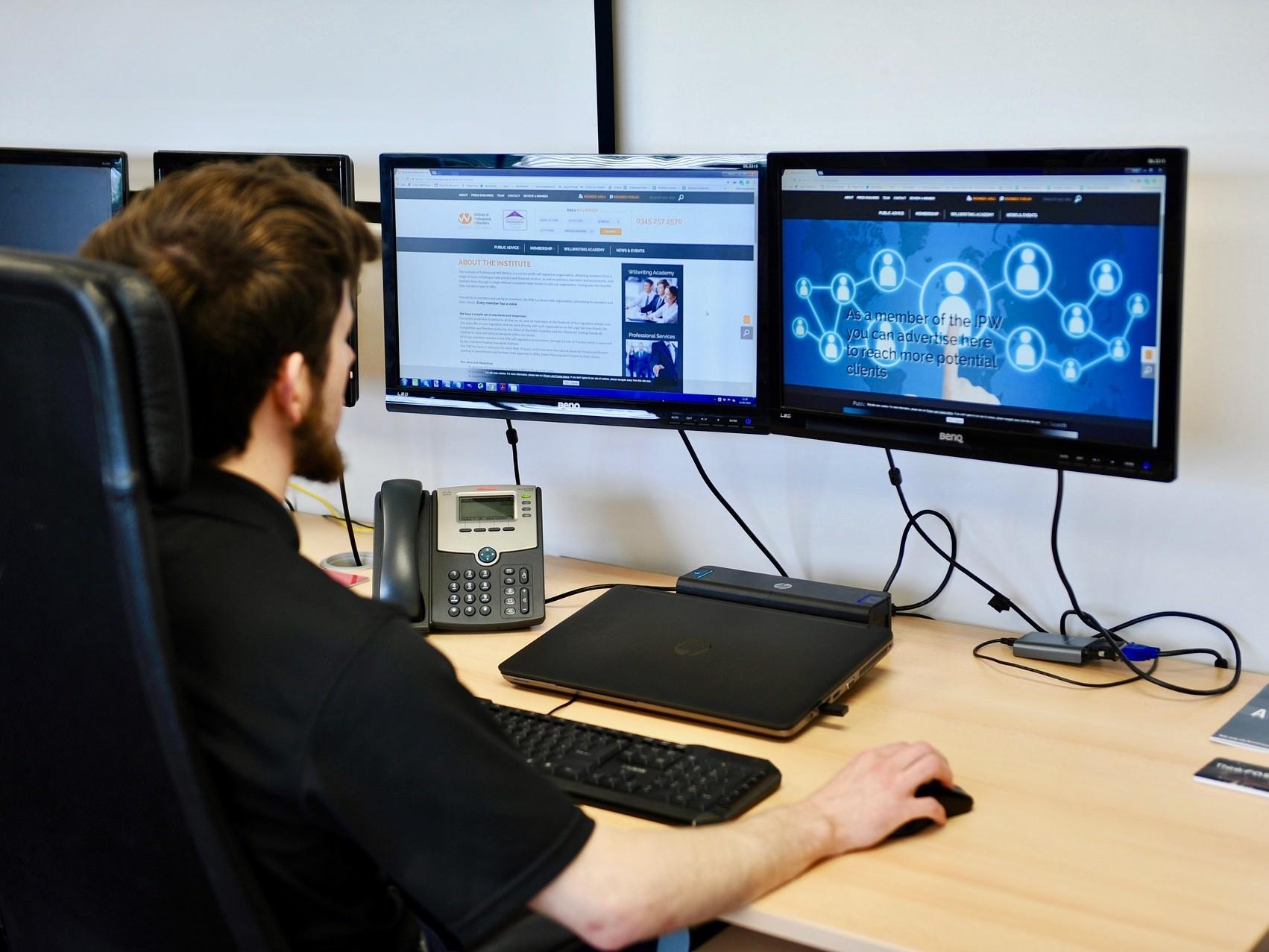 Mann sitzt am Schreibtisch vor zwei Computermonitoren.