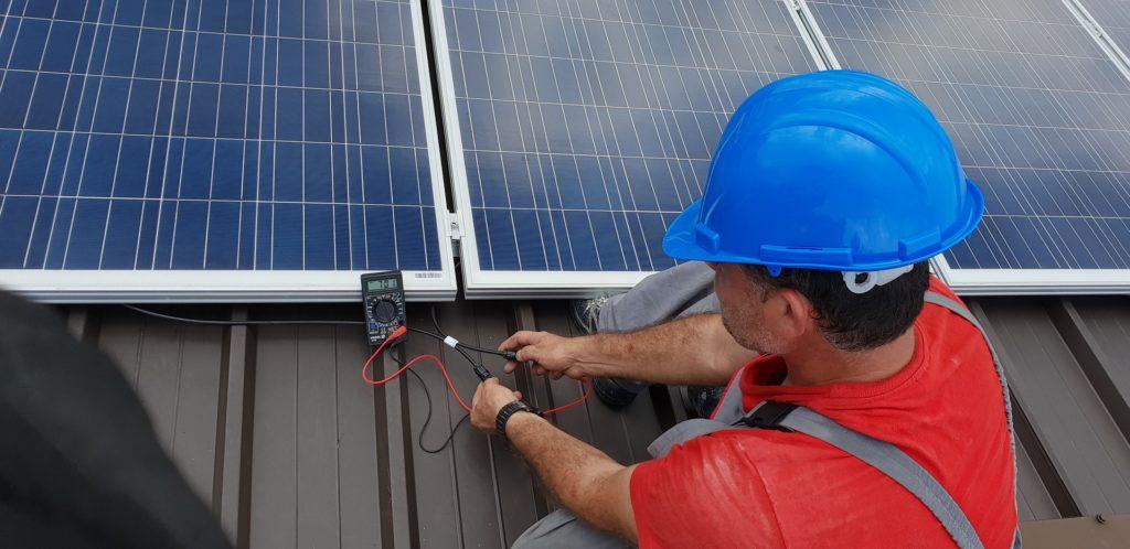 Monteur mit Messgerät vor einem Solarmodul auf dem Dach.