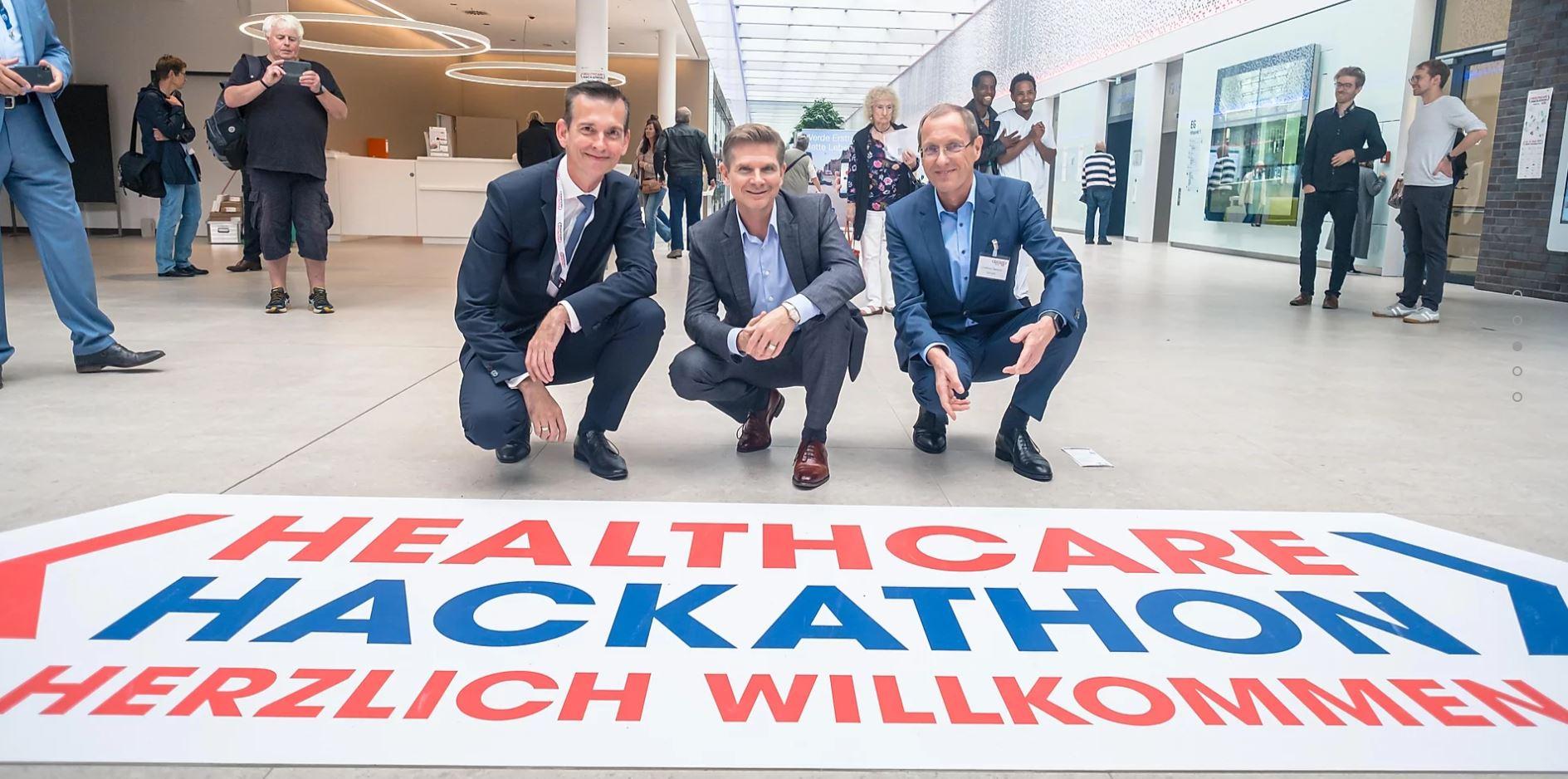 Drei Herren hocken vor dem Logo des Healthcare Hackathons auf dem Boden.