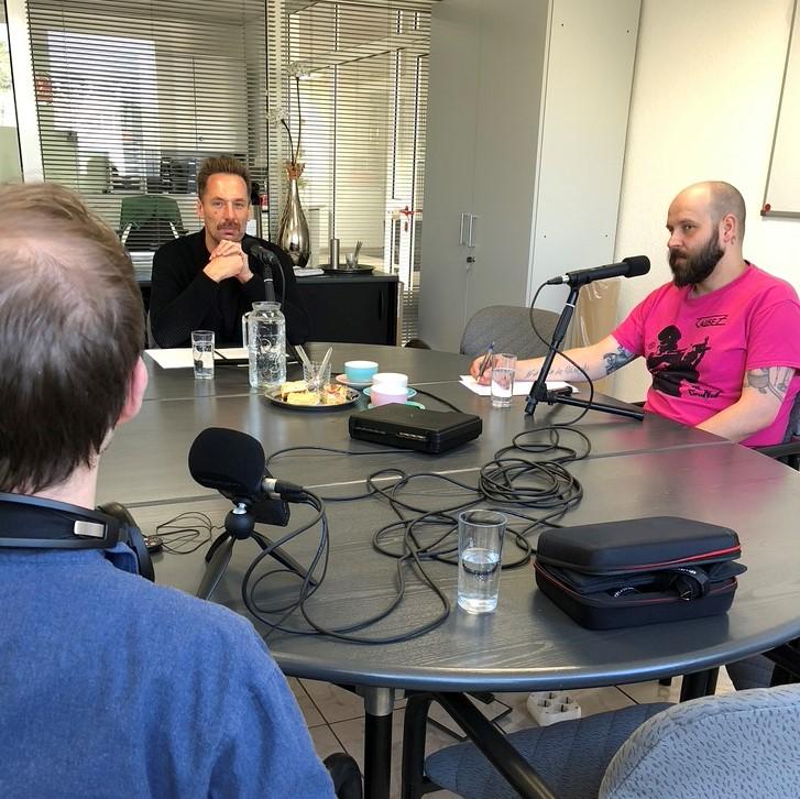 Drei Personen mit Mikrofonen an einem Tisch