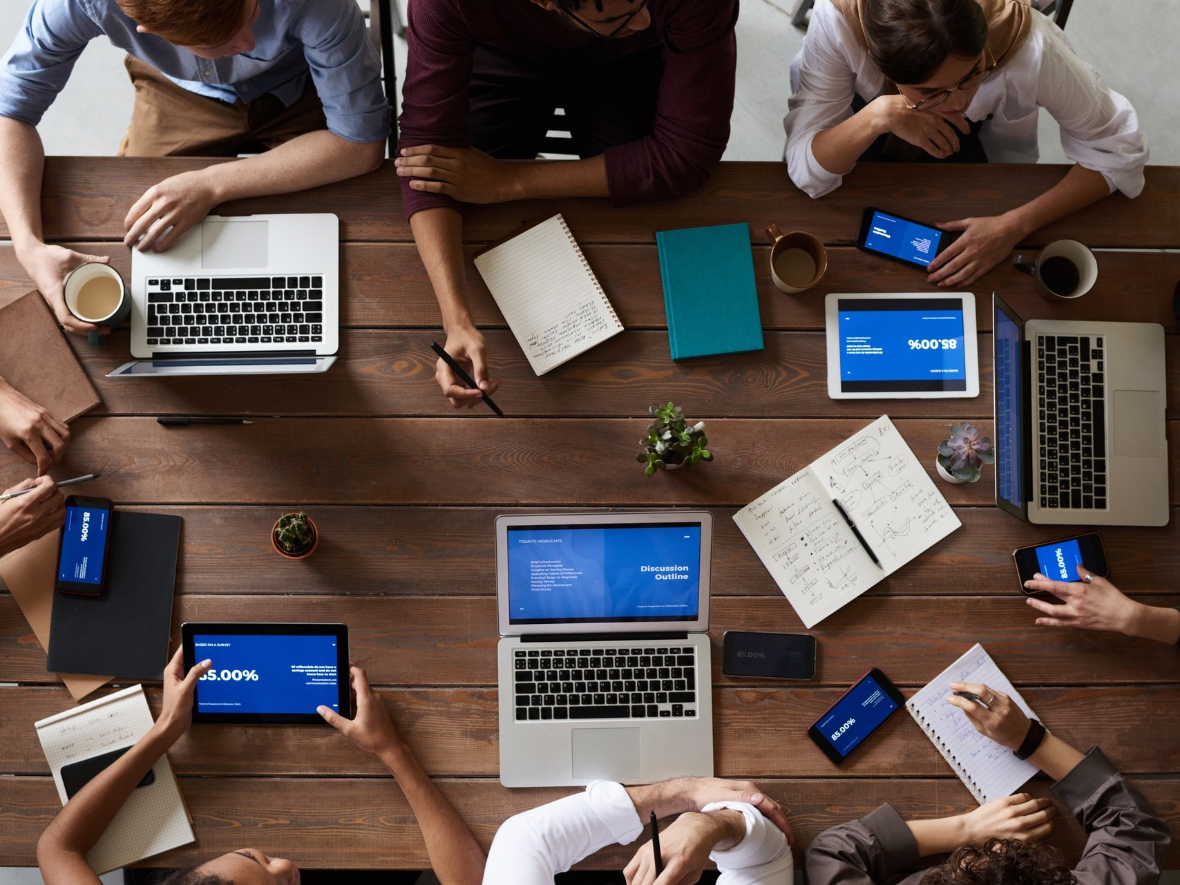 Blick von oben auf einen Schreibtisch, an dem acht Menschen in Teamwork arbeiten.