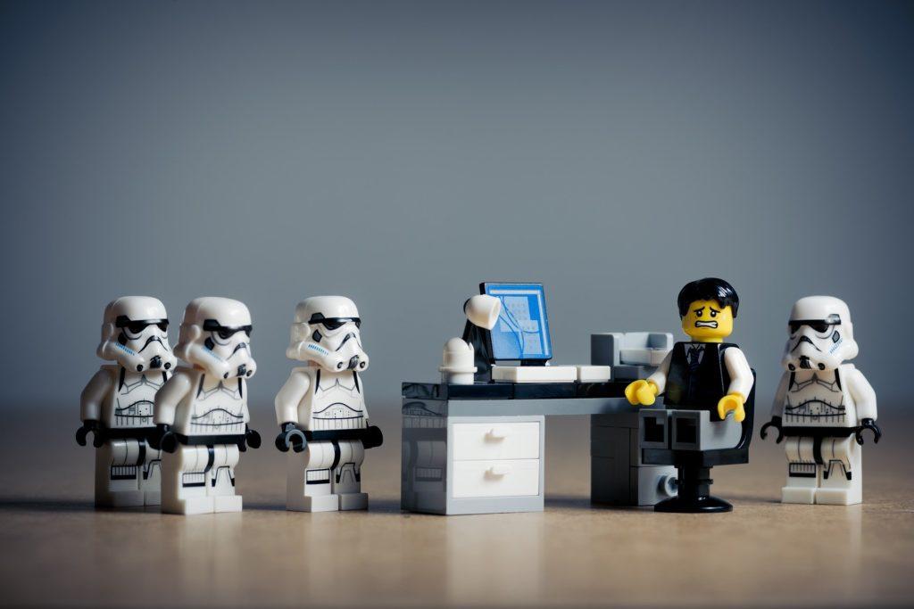 Ein Legomännchen am Schreibtisch wird von vier Lego-Sturmtrupplern umzingelt.
