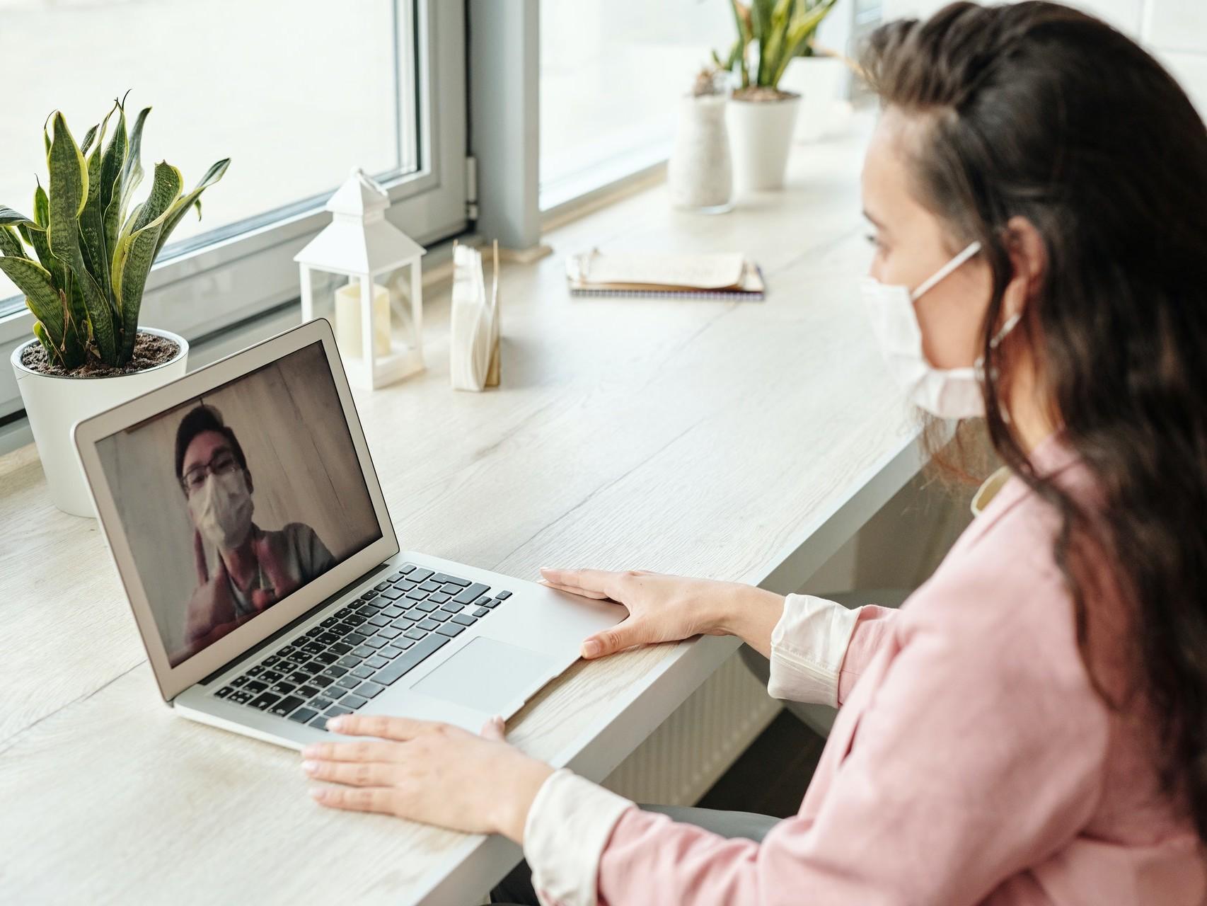 Frau mit Mundschutz sitzt am Laptop und hat eine Videosprechstunde mit einem Mann mit Mundschutz.