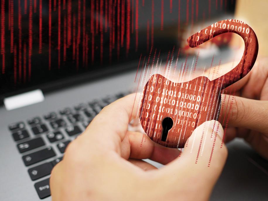 Symbolbild Sicherheit im Internet, Hände halten Vorhängeschloss vor einen Laptop.