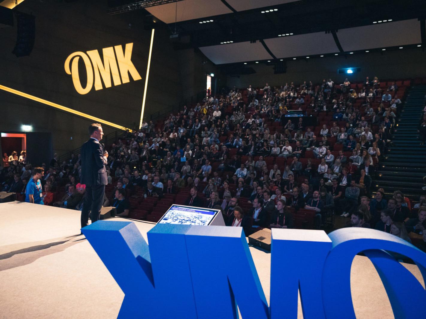 Blick auf einen Redner bei der OMK Lüneburg vor einem vollbesetzten Hörsaal.