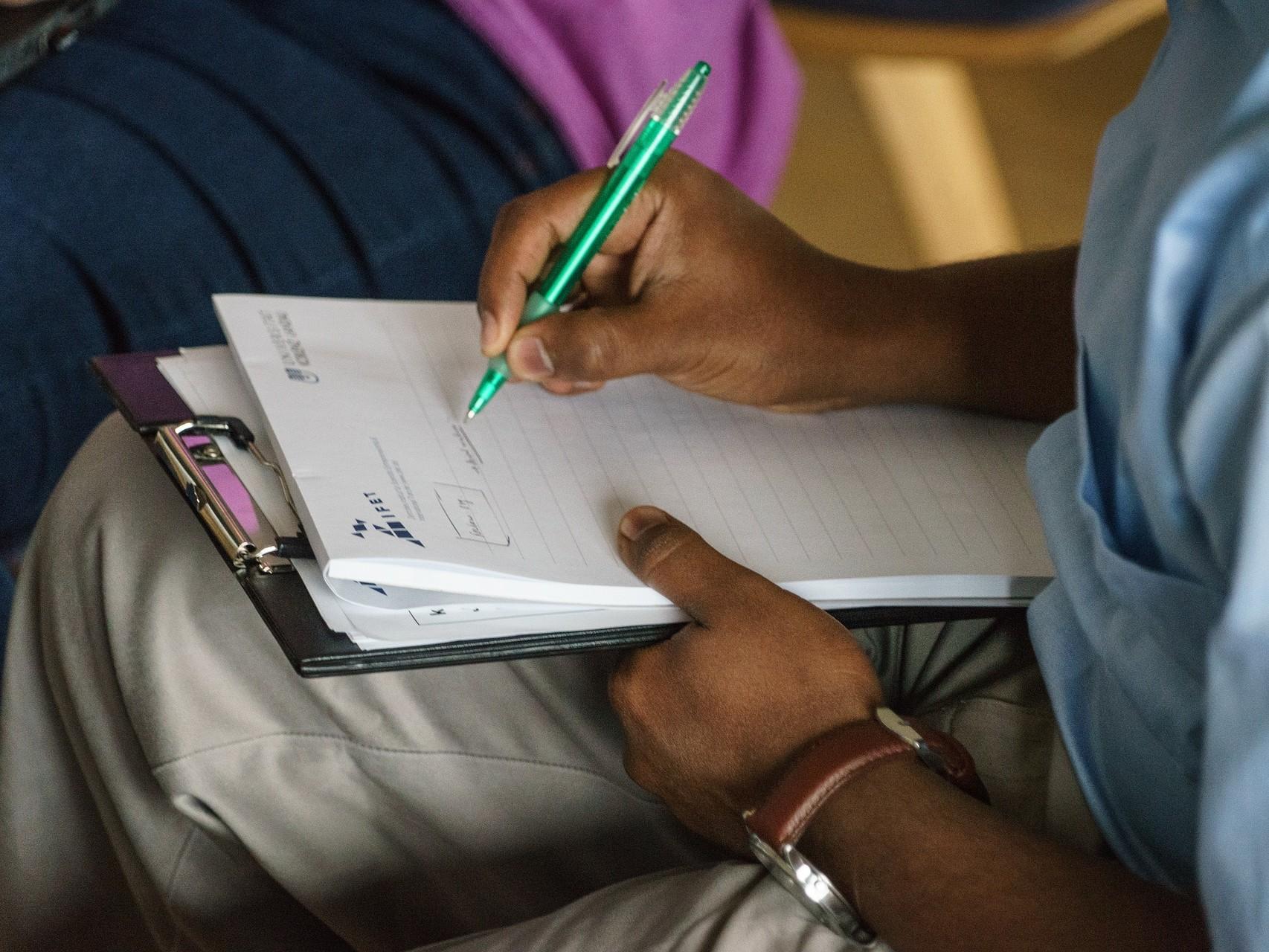 Mann sitzt im Unterricht und macht sich Notizen auf einem Block auf seinen Knien.
