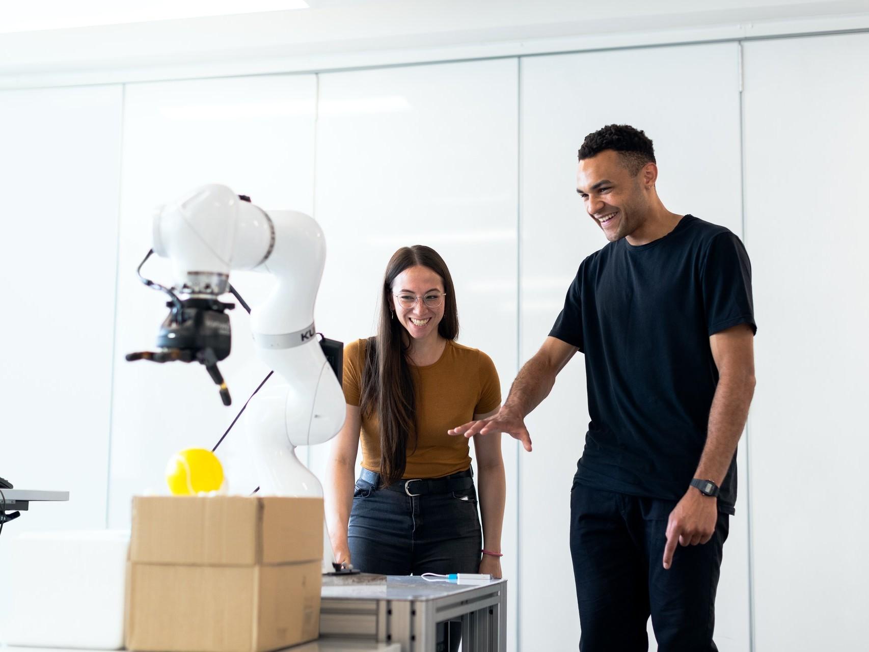 Junge Frau und junger Mann stehen in einem Raum vor einem weißen Roboterarm.