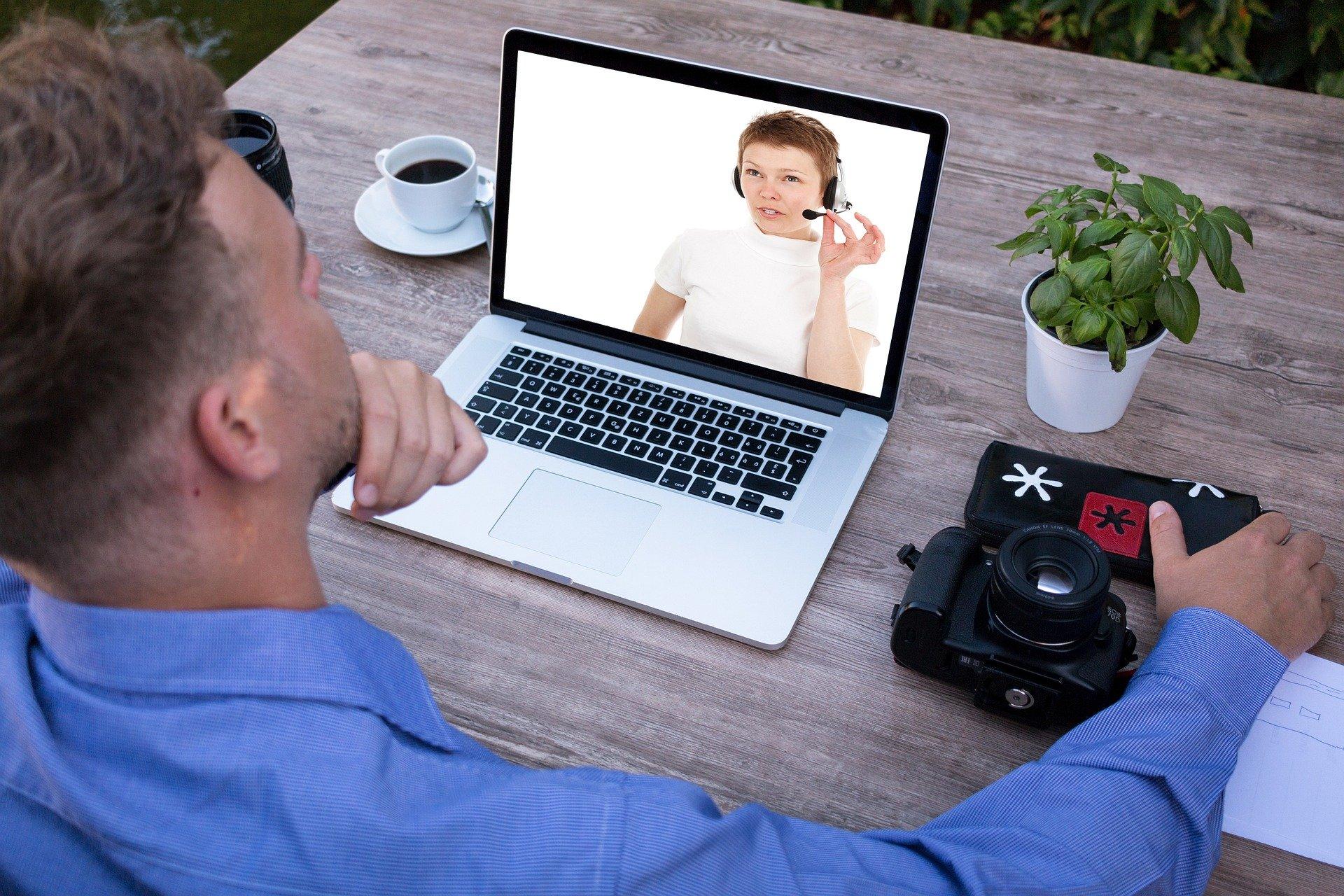 Mann sitzt vor einem Laptop und nimmt an einem Webinar teil.