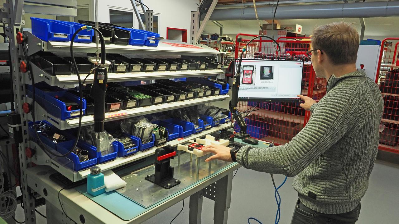 Ein Mitarbeiter der Esders GmbH steht vor einem Werkertisch und nutzt einen Monitor.