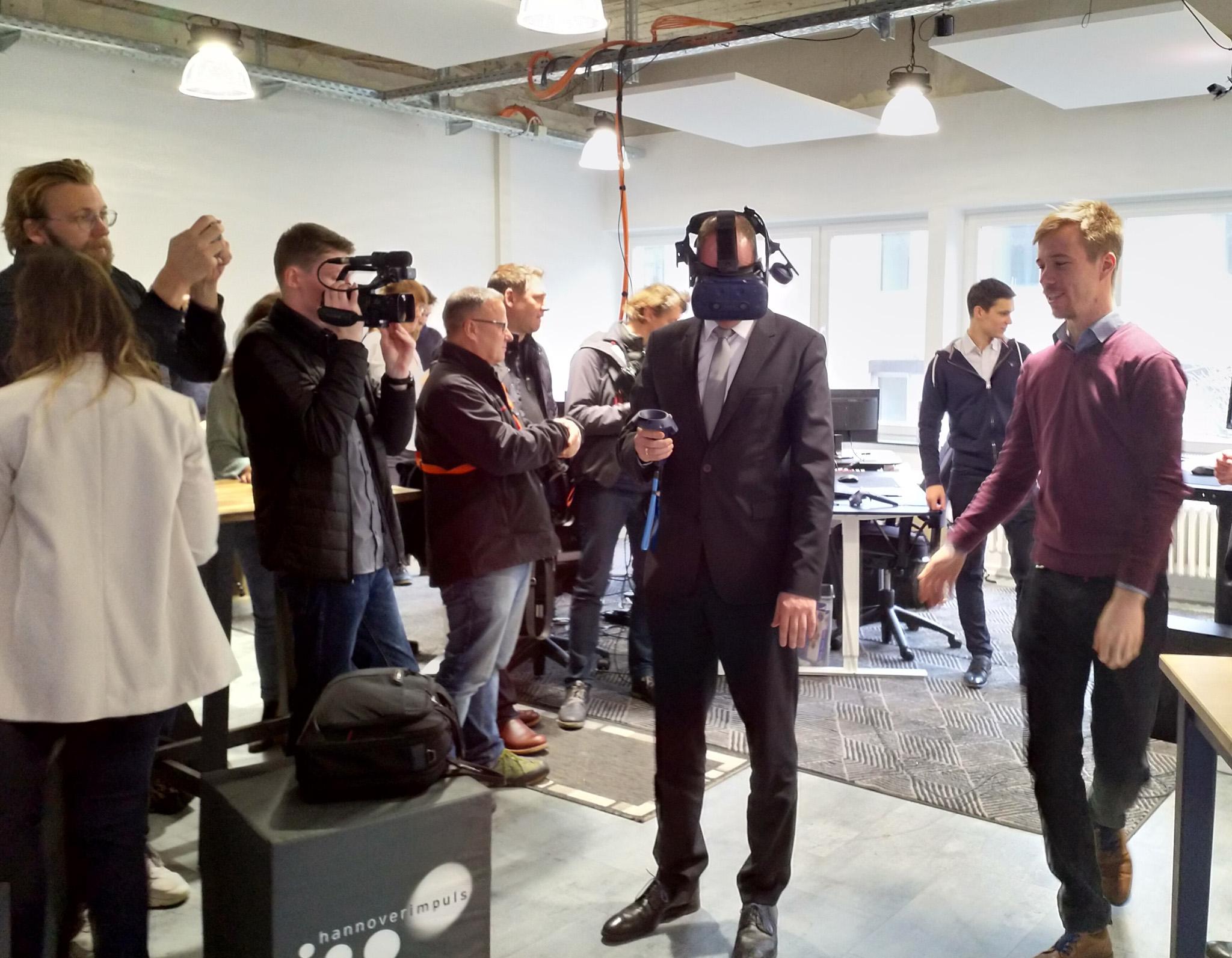 Männer und Frauen stehen im VR-Lab. Einige probieren Virtual-Reality-Hardware aus.