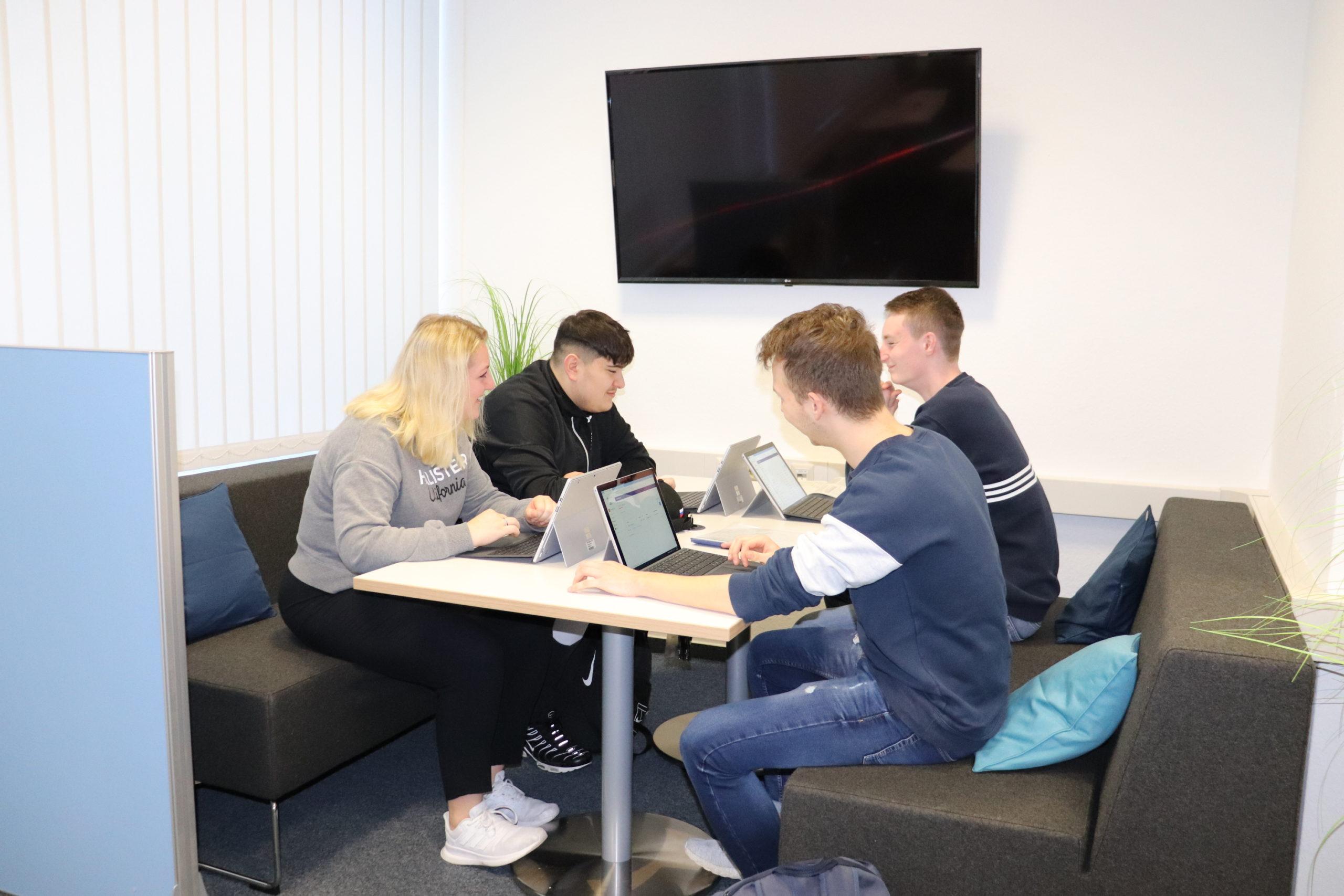 Drei Schüler und eine SChülerin sitzen am Tisch und lernen digital mit Laptops.