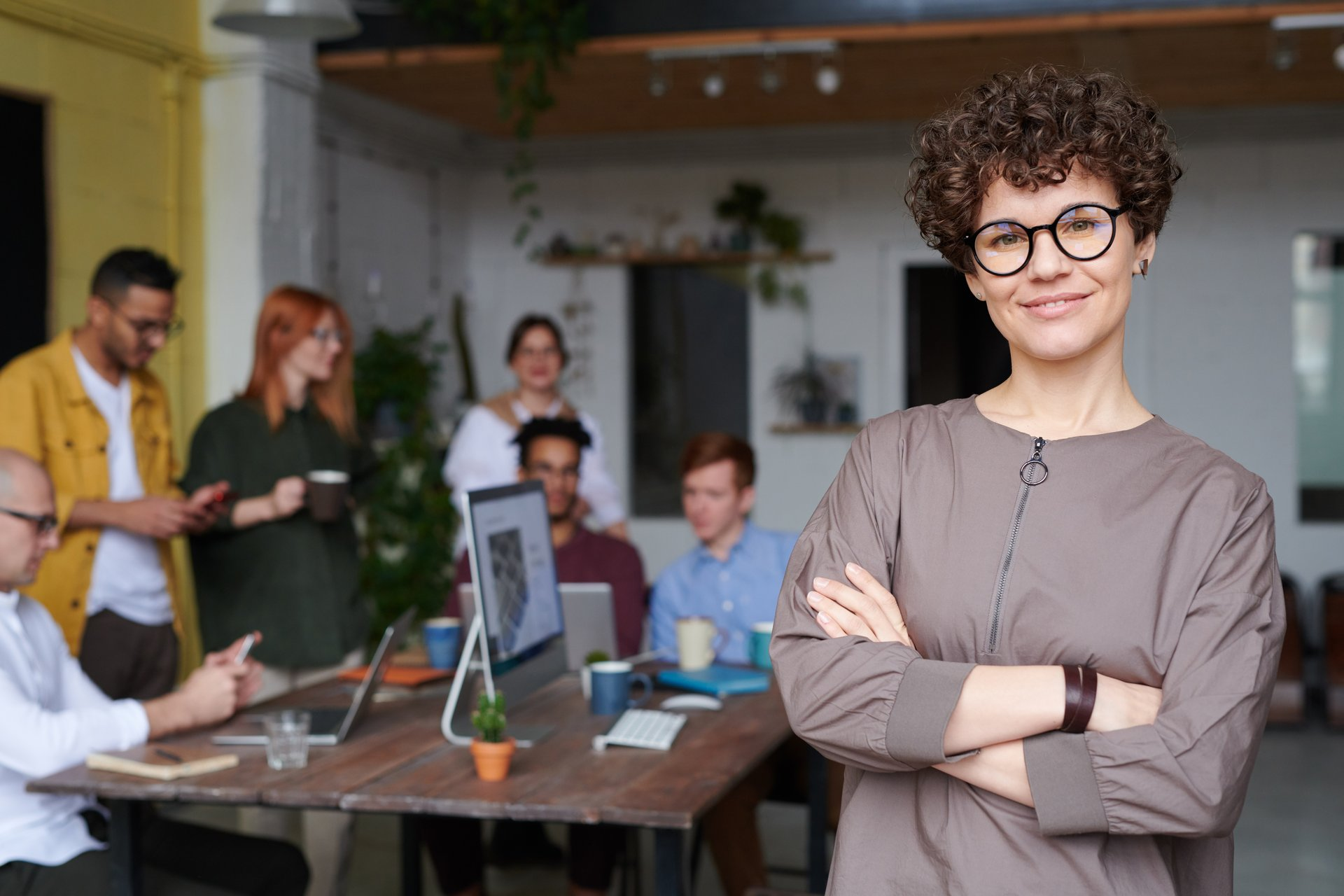 Frau mit Brille schaut in Kamera, hinter ihr sitzen Menschen im Meeting am Schreibtisch.