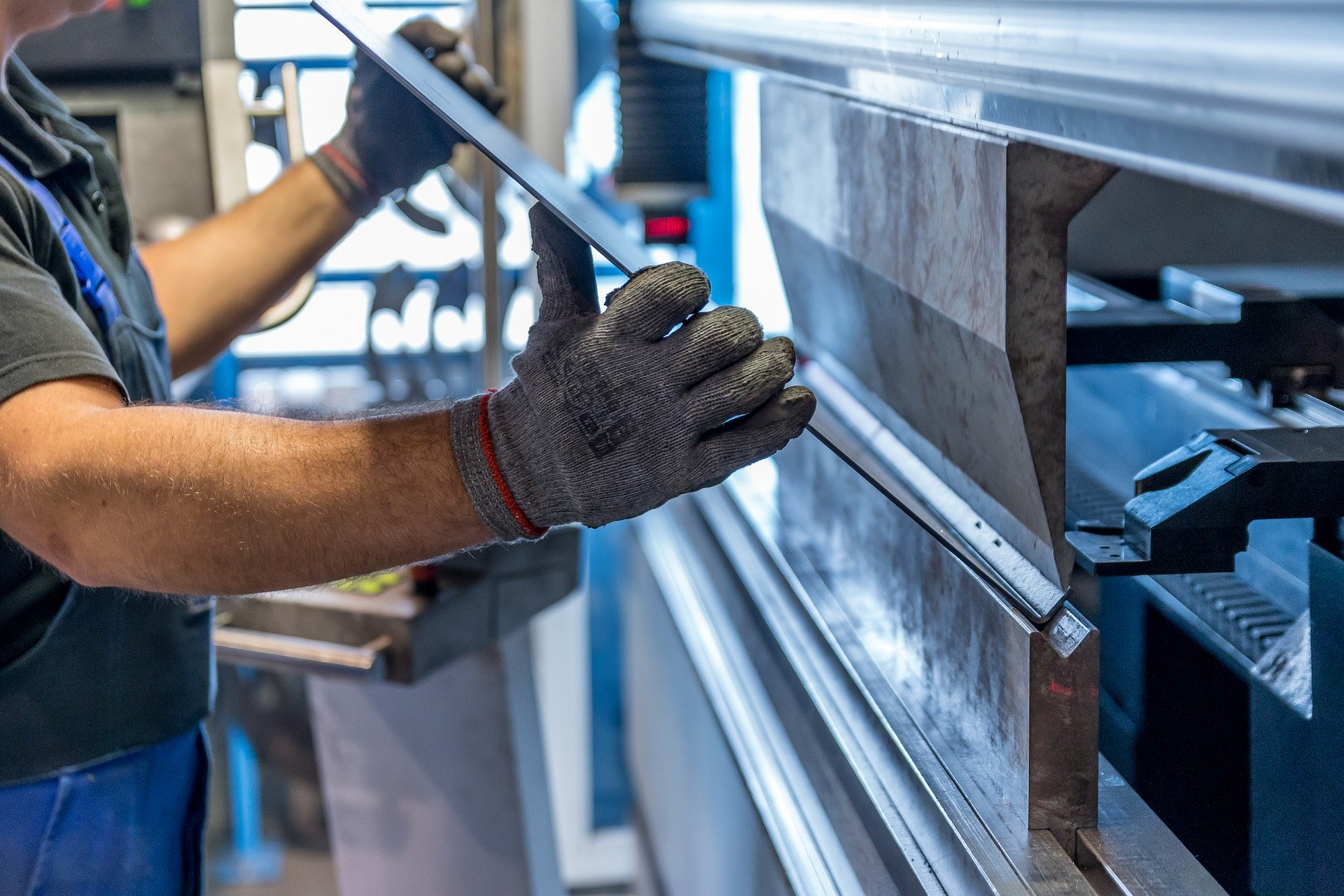 An einer Maschine wird durch einen Arbeitenden ein Metallstück bearbeitet.