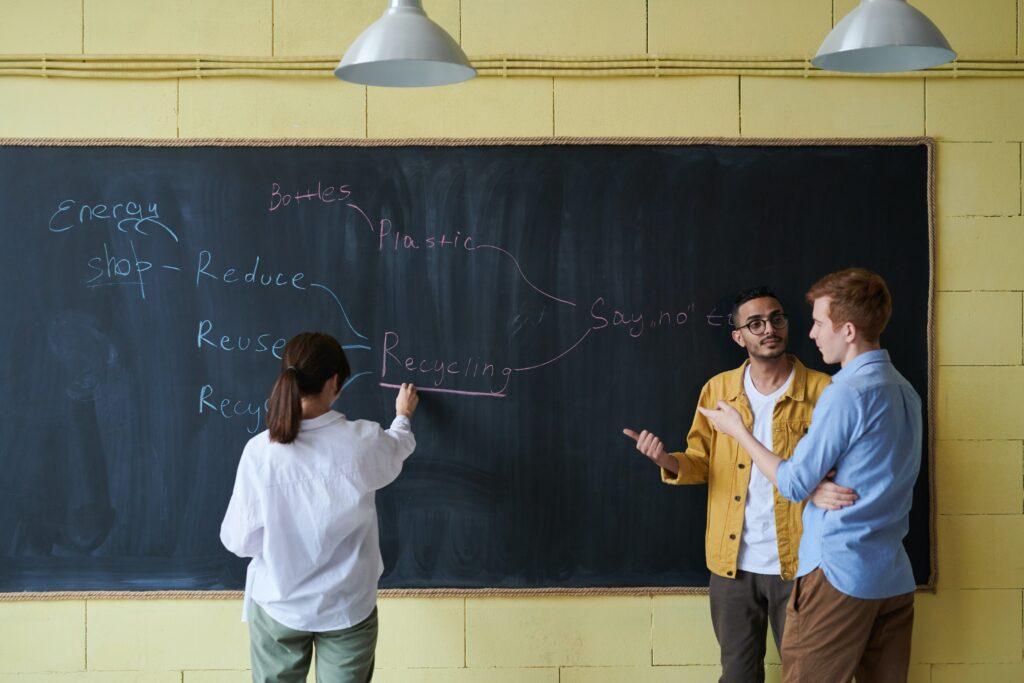 Frau steht an der Tafel und schreibt, zwei Männer stehen daneben.