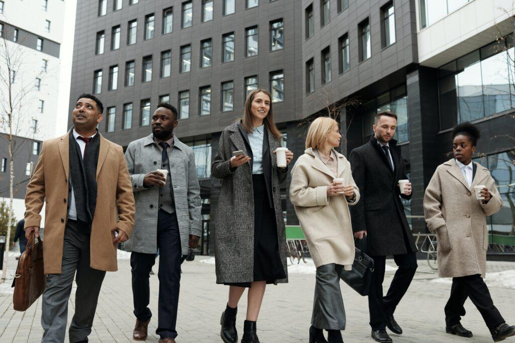 Drei Frauen und drei Männer nebeneinander auf der Straße bei der Mittagspause.