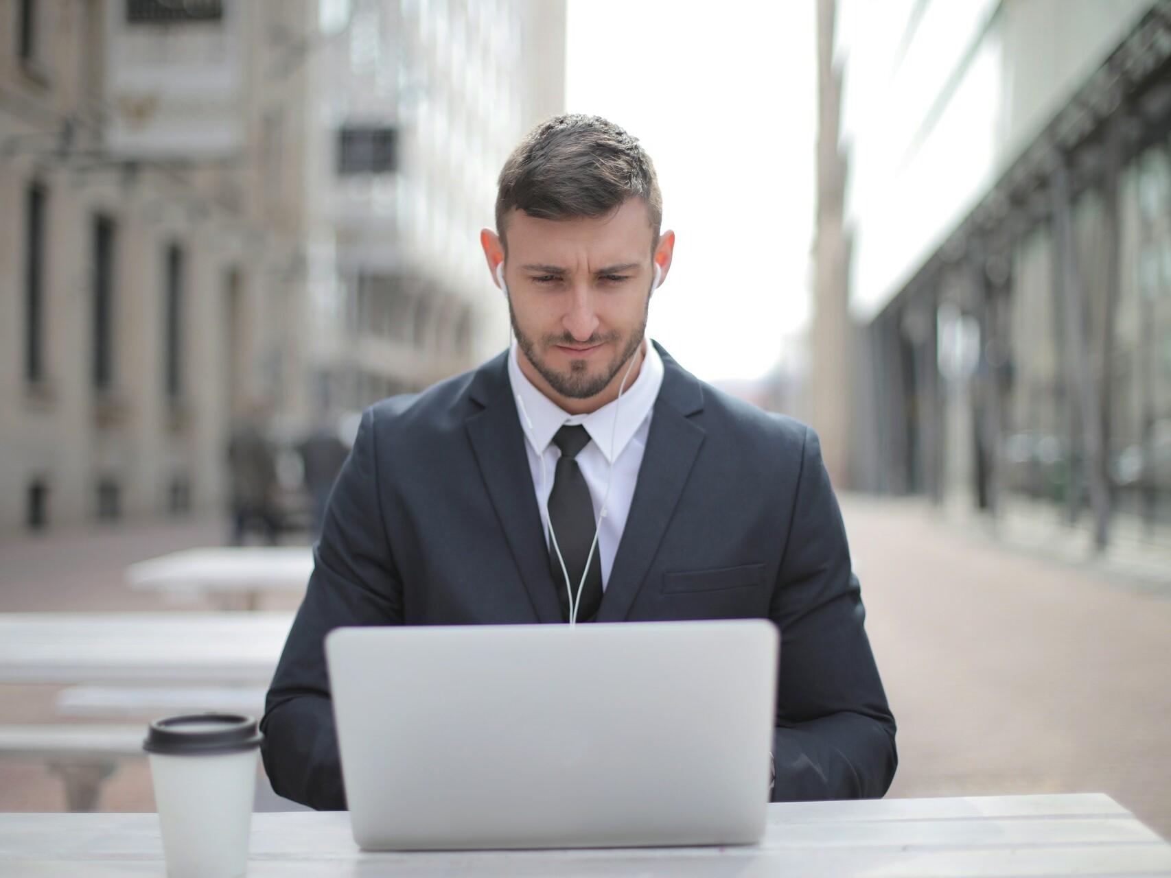 Mann sitzt am Tisch in der Fußgängerzone ganz allein am Laptop.
