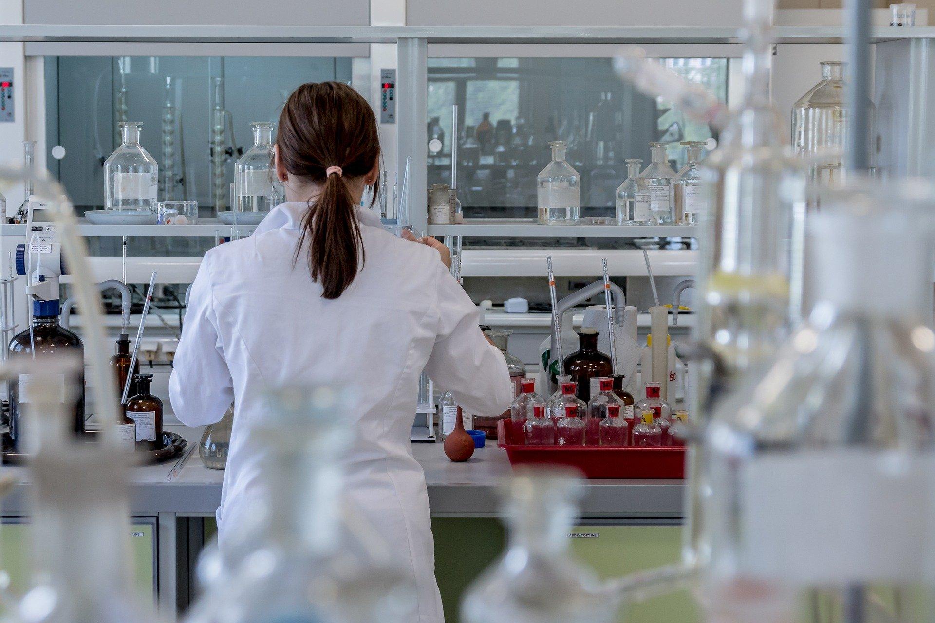 Frau in weißem Kittel steht im Labor mit dem Rücken zur Kamera.