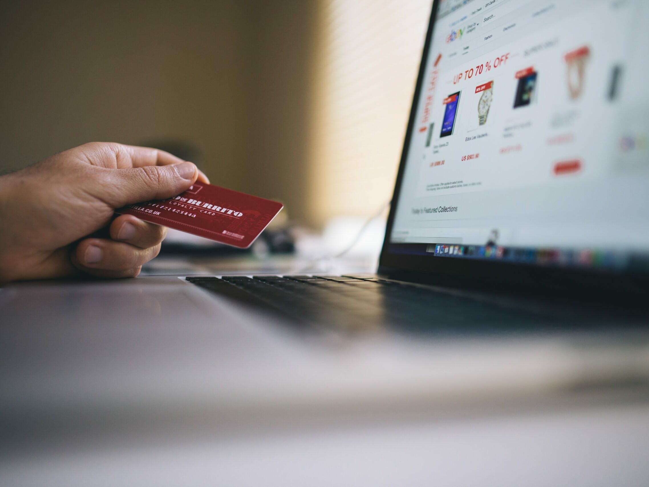 Eine Person vor einem Laptop mit einer Kreditkarte in der Hand.