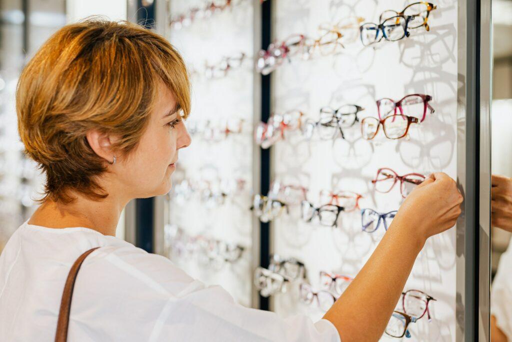 Eine Frau beim Optiker vor einem Regal mit zahlreichen Brillen.