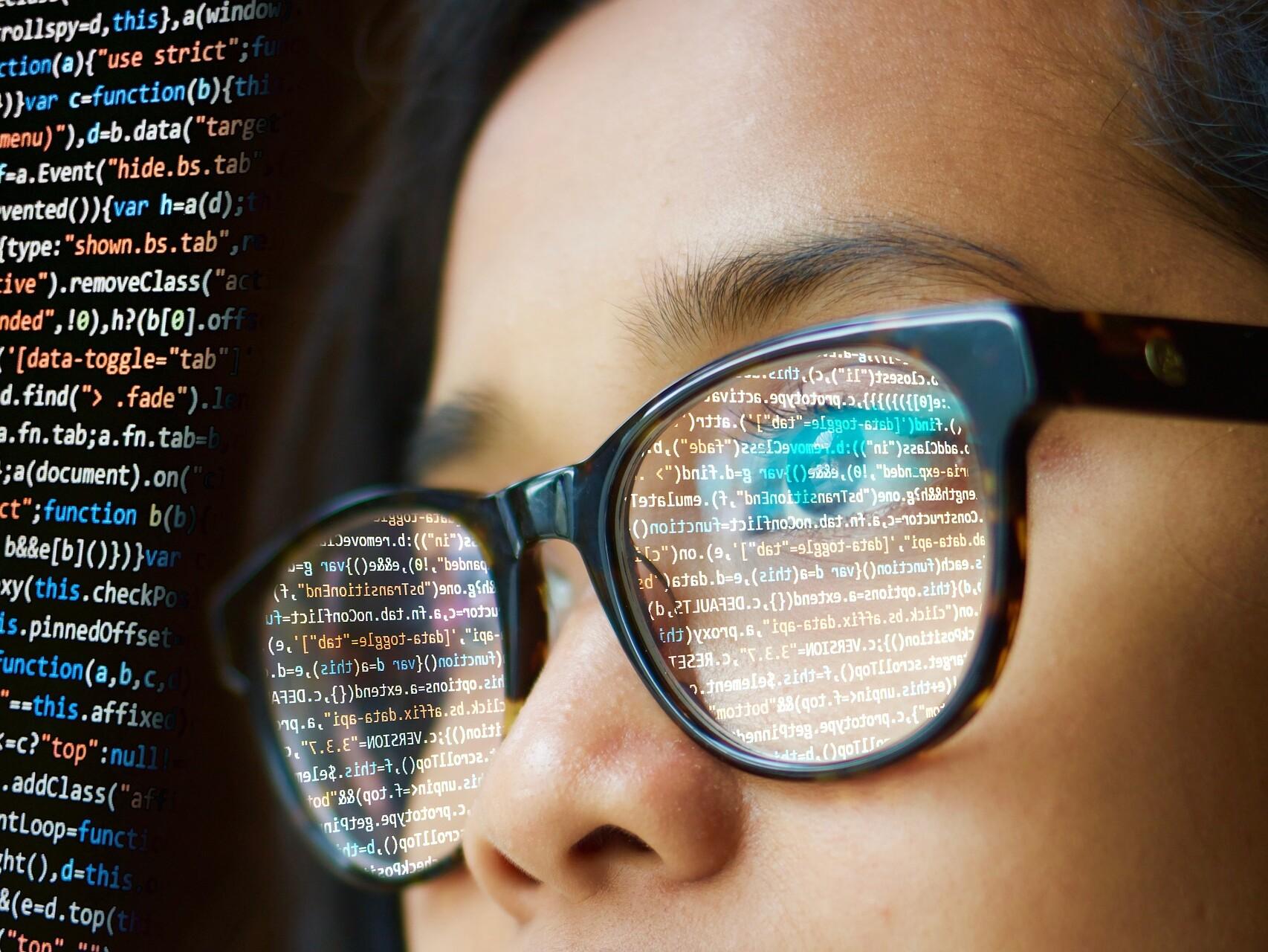 Frau mit Brille schaut auf einen Computerbildschirm mit Programmiersprache.