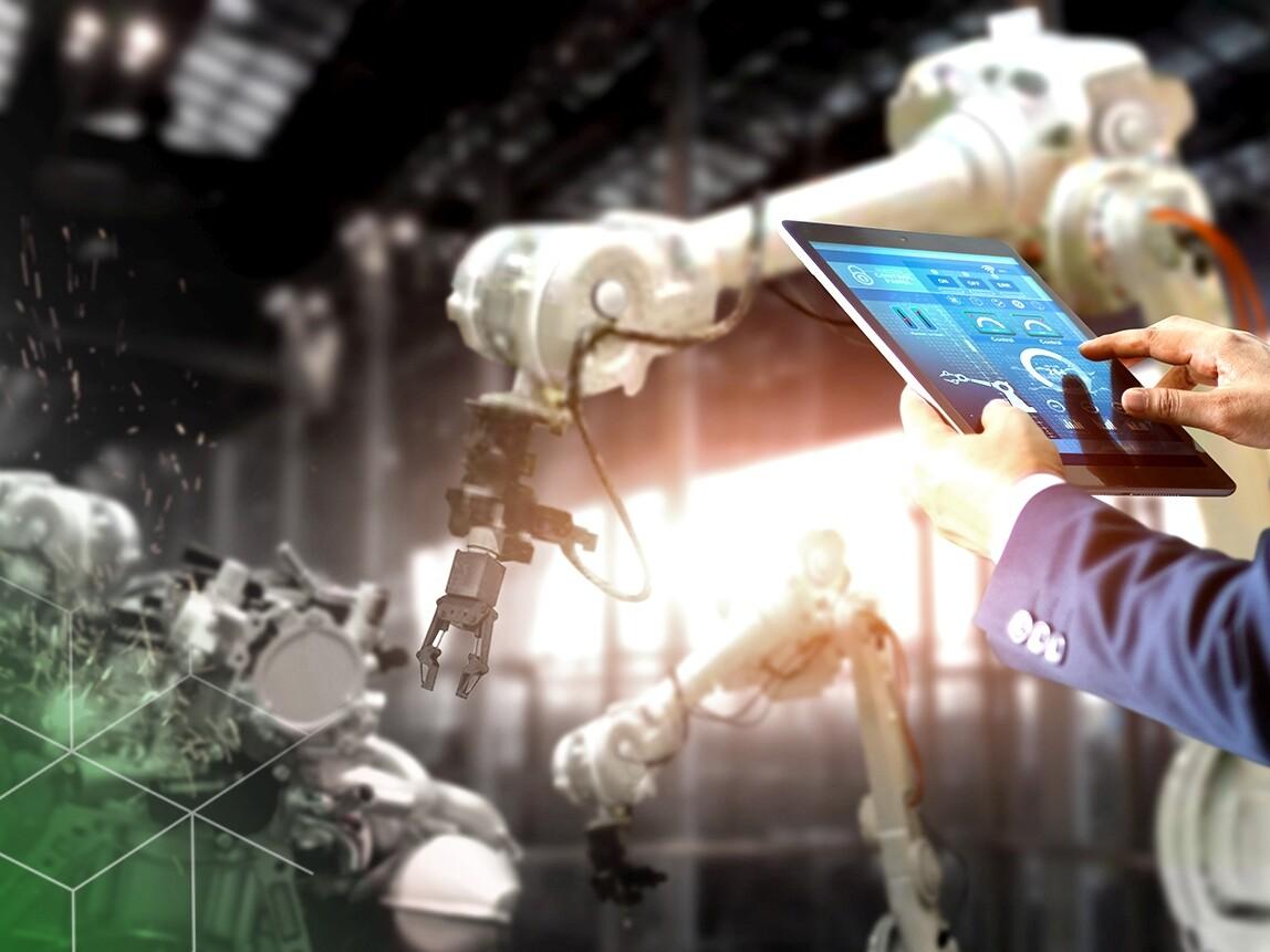 Eine Person mit einem Tablet in der Hand steuert einen Roboterarm.