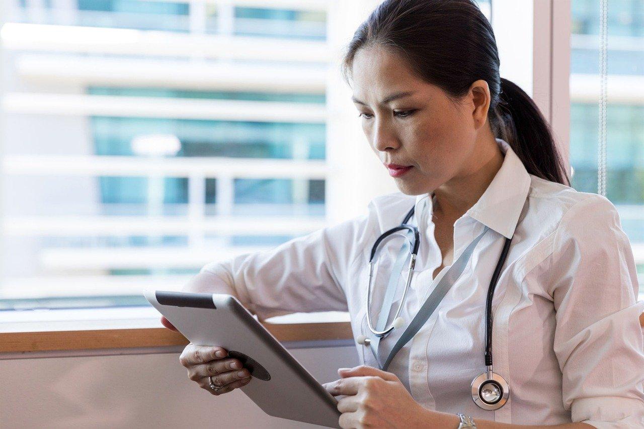 Ärztin sitzt am Fenster und hat ein Tablet in der Hand.
