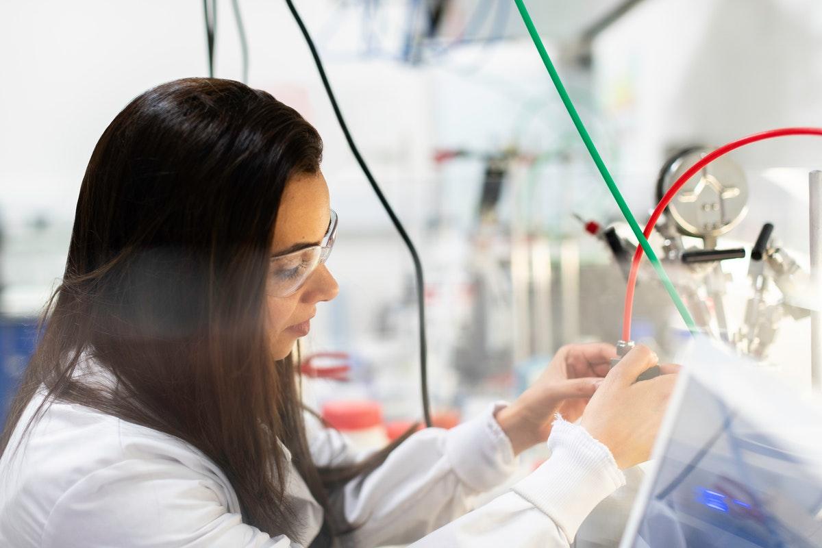 Ingenieurin im Labor vor einem Tisch mit Apparaten und Leitungen.