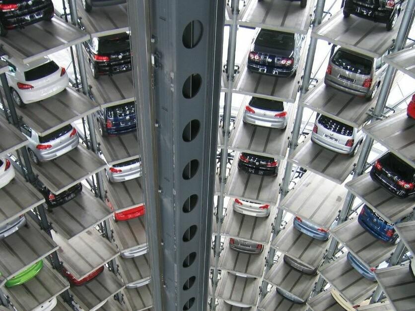 Blick ins Halbrund eines riesigen Hochregallagers mit dutzenden Autos.