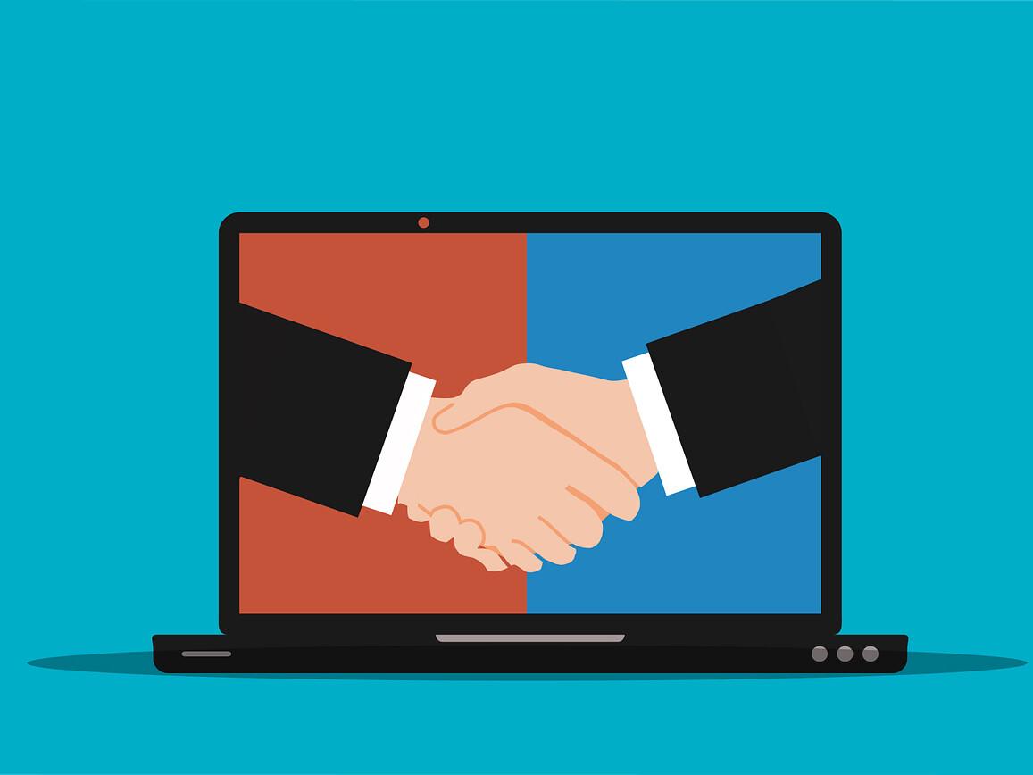Symbolbild für Geschäftsabschluss. Handschlag auf einem Laptop-Monitor