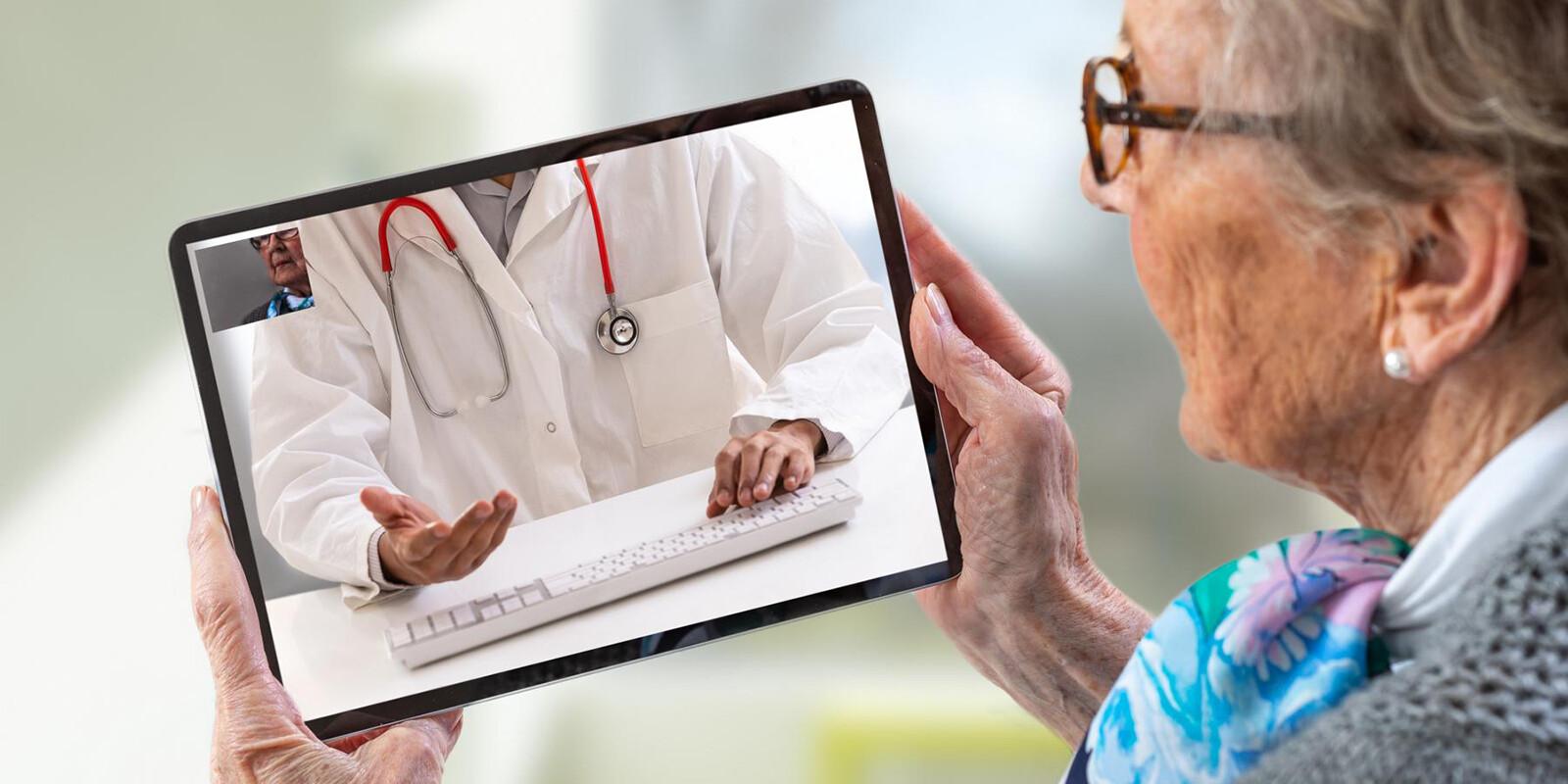 Seniorin spricht über das Tablet mit ihrem Arzt