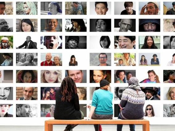 Symbolbild UpdateDeutschland: Drei Personen sitzen vor einer Wand, auf der zahlreiche Fotos von diversen Menschen zu sehen sind.