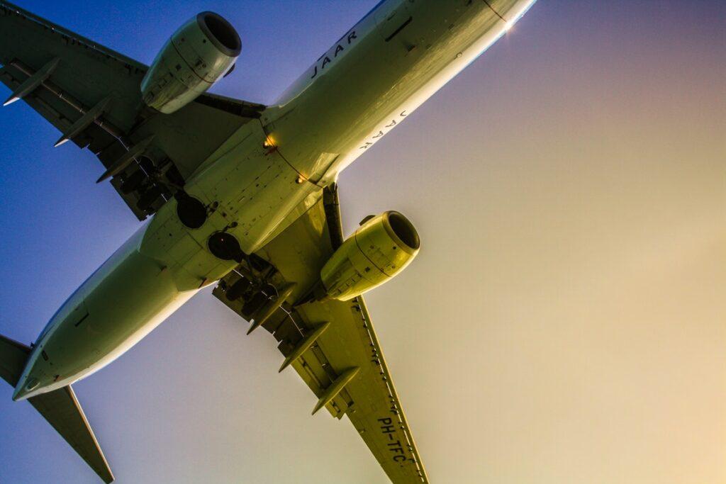 Blick von unten auf die Unterseite eines startenden Flugzeugs mit Triebwerk und Tragflächen.