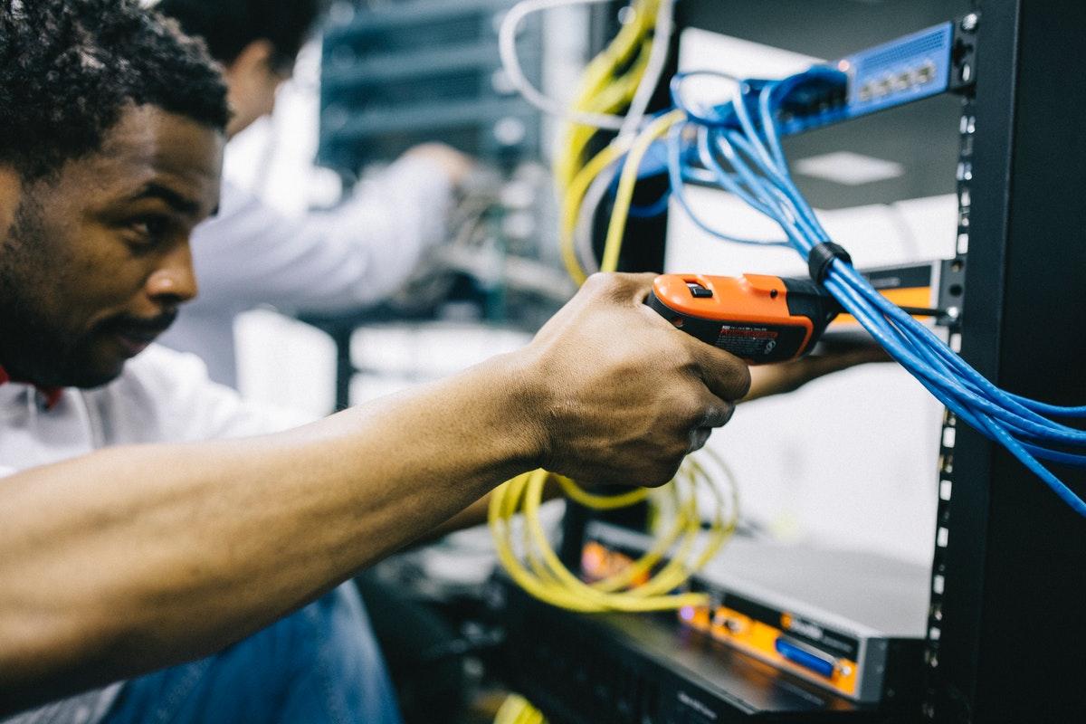 Ein Mann mit einem Werkzeug bei der Montage an einem Element im Serverraum.