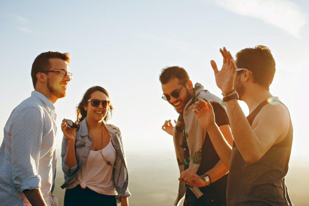 Eine Gruppe aus drei Männern und einer Frau stehen gut gelaunt im Sonnenlicht zusammen.