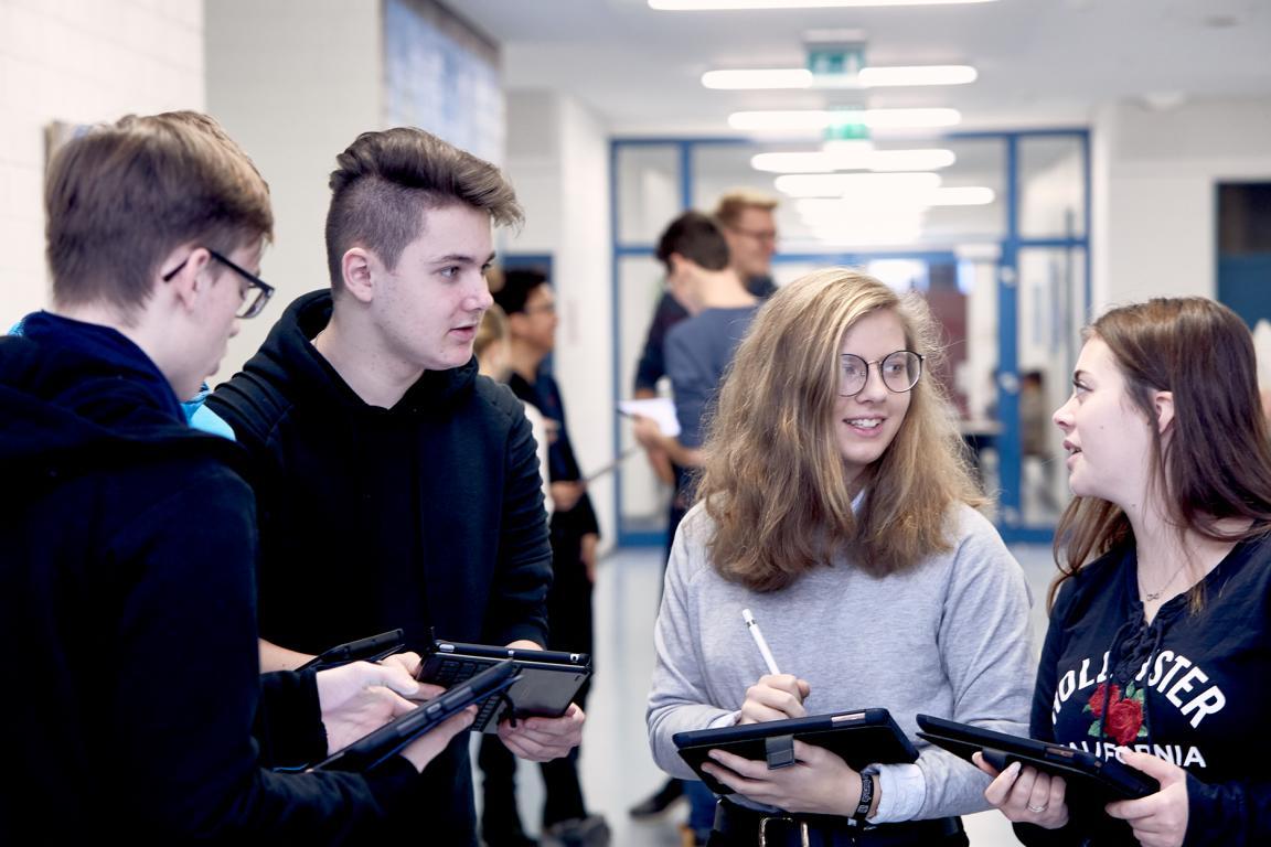 Das Bild zeigt eine Gruppe von Schülern mit Tablets auf dem Arm.