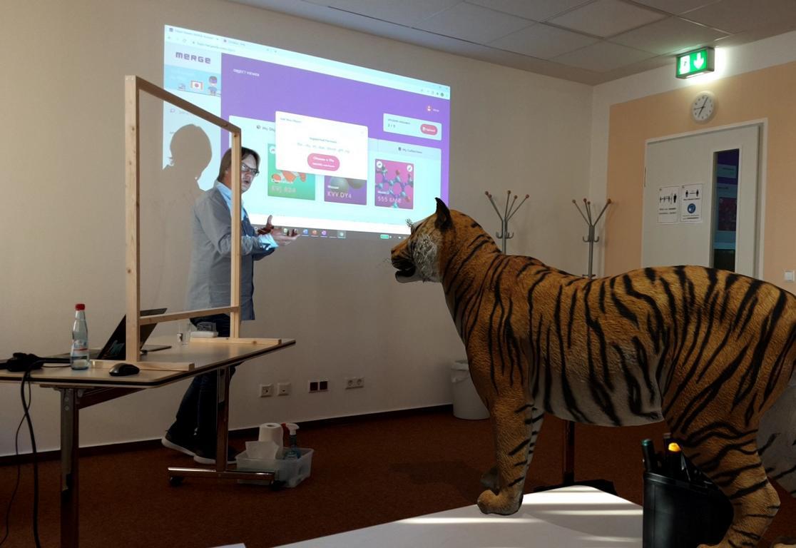 Das Foto zeigt einen Referenten, der den Teilnehmenden einen AR-Tiger zeigt.